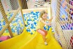 Happy little girl having fun in ball pit in kids indoor play center. Child playing with colorful balls in playground ball pool. Activity toys for little kids Stock Photos