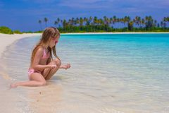 Happy little girl having fun at shallow water at stock images