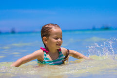 Happy little girl having fun, swimming and jumping Stock Image