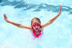 Happy little girl having fun in swimming pool stock photo