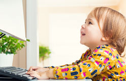 Happy little girl having fun using her computer Stock Photography