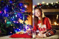 Happy little girl having milk and cookies by a fireplace in a cozy dark living room on Christmas eve Royalty Free Stock Photos