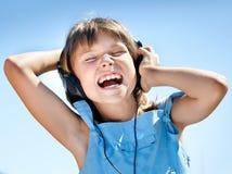 Happy little girl in headphones Stock Photo