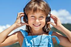 Happy little girl in headphones stock photography