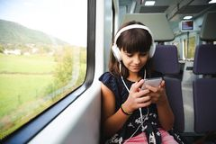 Little girl with headphones and smart phone travelling by train royalty free stock photo