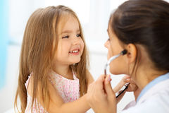 Happy little girl at health exam at doctor office. Medicine and health care concept.  stock photo