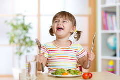 Happy little girl with healthy food for dinner Stock Photo