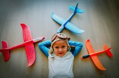 Happy little girl with helmet and glasses play with toy planes. Little pilot royalty free stock image