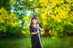 Happy little girl help parents in garden with rake. Seasonal garden work. Backyard cleaning Royalty Free Stock Photos