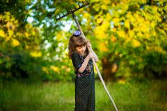 Happy little girl help parents in garden with rake. Seasonal garden work. Backyard cleaning Stock Photography