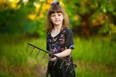Happy little girl help parents in garden with rake. Seasonal garden work. Backyard cleaning Royalty Free Stock Images