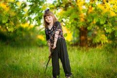 Happy little girl help parents in garden with rake. Seasonal garden work. Backyard cleaning Stock Photos