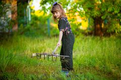 Happy little girl help parents in garden with rake. Seasonal garden work. Backyard cleaning Stock Image