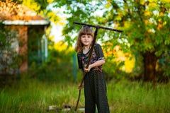 Happy little girl help parents in garden with rake. Seasonal garden work. Backyard cleaning Royalty Free Stock Image