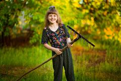 Happy little girl help parents in garden with rake. Seasonal garden work. Backyard cleaning Stock Images