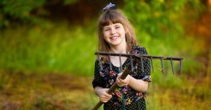 Happy little girl help parents in garden with rake. Seasonal garden work. Backyard cleaning Royalty Free Stock Photo