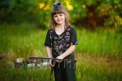 Happy little girl help parents in garden with rake. Seasonal garden work. Backyard cleaning Stock Photo