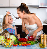 Happy little girl helping mother to cook Stock Images