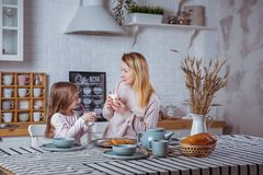 Happy little girl and her beautiful young mother have breakfast together in a white kitchen. They drink milk and eat cookies. stock photo