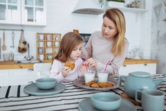 Happy little girl and her beautiful young mother have breakfast together in a white kitchen. They drink milk and eat cookies. stock image