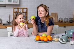 Happy little girl and her beautiful young mother have breakfast together in a white kitchen. They are having fun and eating apples stock image