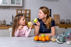 Happy little girl and her beautiful young mother have breakfast together in a white kitchen. They are having fun and eating apples stock photography