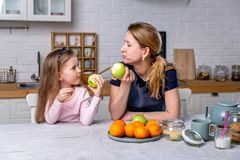 Happy little girl and her beautiful young mother have breakfast together in a white kitchen. They are having fun and eating apples stock photo