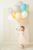 Happy little girl with her birthday cake and colorful balloons in room. Stock Photo