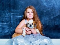 Girl with her dog against chalkboard royalty free stock photo