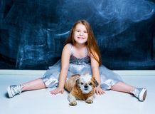 Girl with her dog against chalkboard stock photography