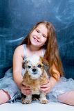 Girl with her dog against chalkboard stock image