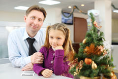 Happy little girl and her father sit in realtor office Stock Photos