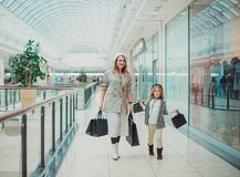 Happy little girl with her mom in shopping cart and her parents enjoying weekend in large trade center stock photo