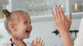 Happy little girl with her mother clap their hands in the kitchen stock photography