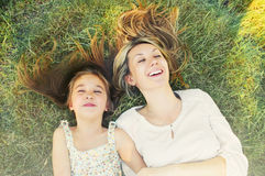Happy little girl and her mother having fun on the grass in sunn Royalty Free Stock Photos