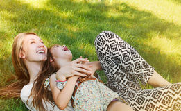 Happy little girl and her mother having fun on the grass in sunn Royalty Free Stock Photo