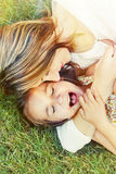 Happy little girl and her mother having fun outdoors on the gras Stock Photo