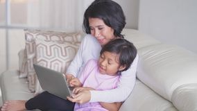 Happy little girl and mother using laptop stock video