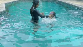 Girl and her mother playing on the pool. Happy little girl and her mother swimming and playing together on the pool while wearing swimsuit stock footage