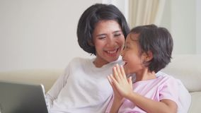 Girl and her mother online shopping with laptop stock footage