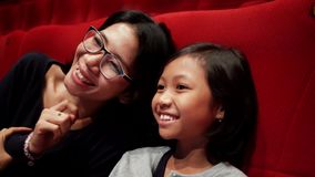 Little girl and mother watching movie in cinema stock video