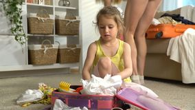 Little Girl with Parents Packing a Luggage for a Journey. Happy little girl with her parents is carefully packing a luggage for a new journey stock video