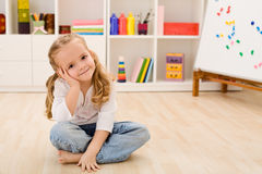 Happy little girl in her room sitting royalty free stock photography