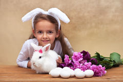 Happy little girl with her spring rabbit and seasonal flowers Royalty Free Stock Photos