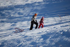 Happy little girl with his mother sledding in the snow mountain Stock Image