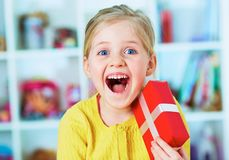 Happy little girl hold red gift. Home portrait Stock Photography