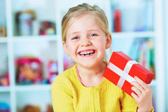 Happy little girl hold red gift. Royalty Free Stock Photo