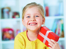Happy little girl hold red gift. Stock Images