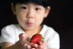 Happy little girl hold a strawberry. Happy little girl put a strawberry in her hand. The focus is on the strawberry Stock Images