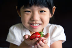 Happy little girl hold a strawberry. Happy little girl put a strawberry in her hand. The focus is on the strawberry Stock Photography